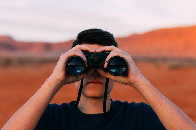 Man peeking through binoculars